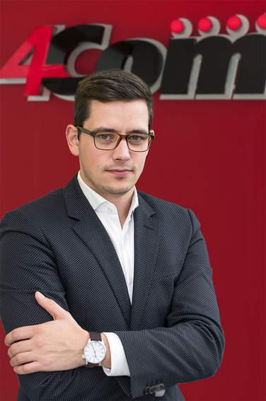 Foto von Marco Kerwitz vor dem 4Com-Logo