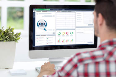 Foto eines Mitarbeiters am Arbeitsplatz mit virtuellem Assistenten